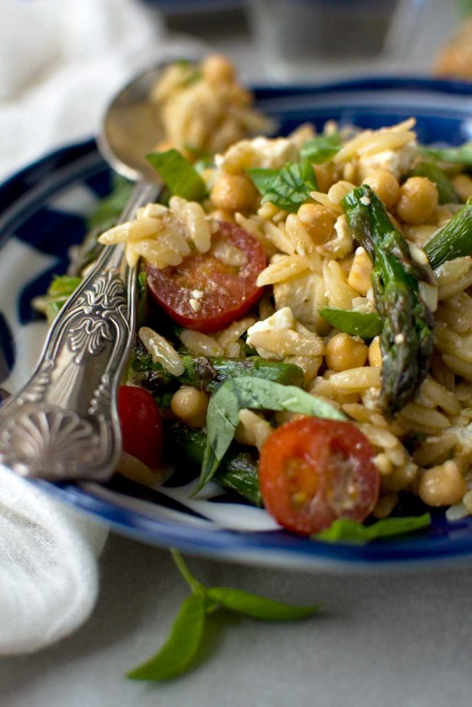 closeup of an Asparagus, tomato and feta orzo salad in a blue patterned dish and with a patterned serving spoon