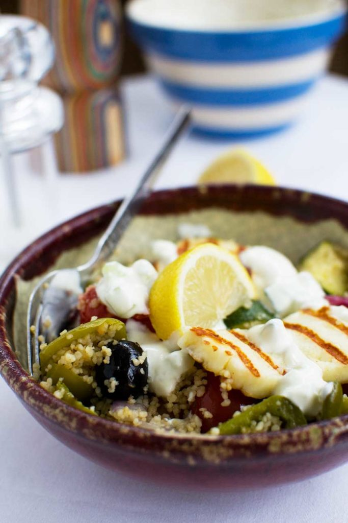 A bowl of Greek couscous with halloumi with a spoon in it