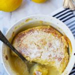 An easy 'magic' lemon pudding from above with lemons and a blue tea towel in the background