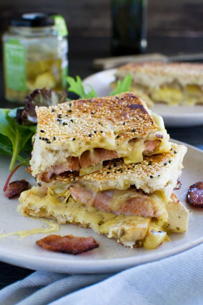 Artichoke and bacon grilled cheese sandwich on a white plate with another sandwich and ingredients in the background