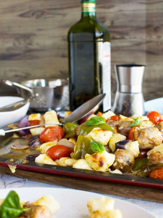 Easy baked gnocchi with sausage, peppers and tomatoes on a baking tray with ingredients in the background