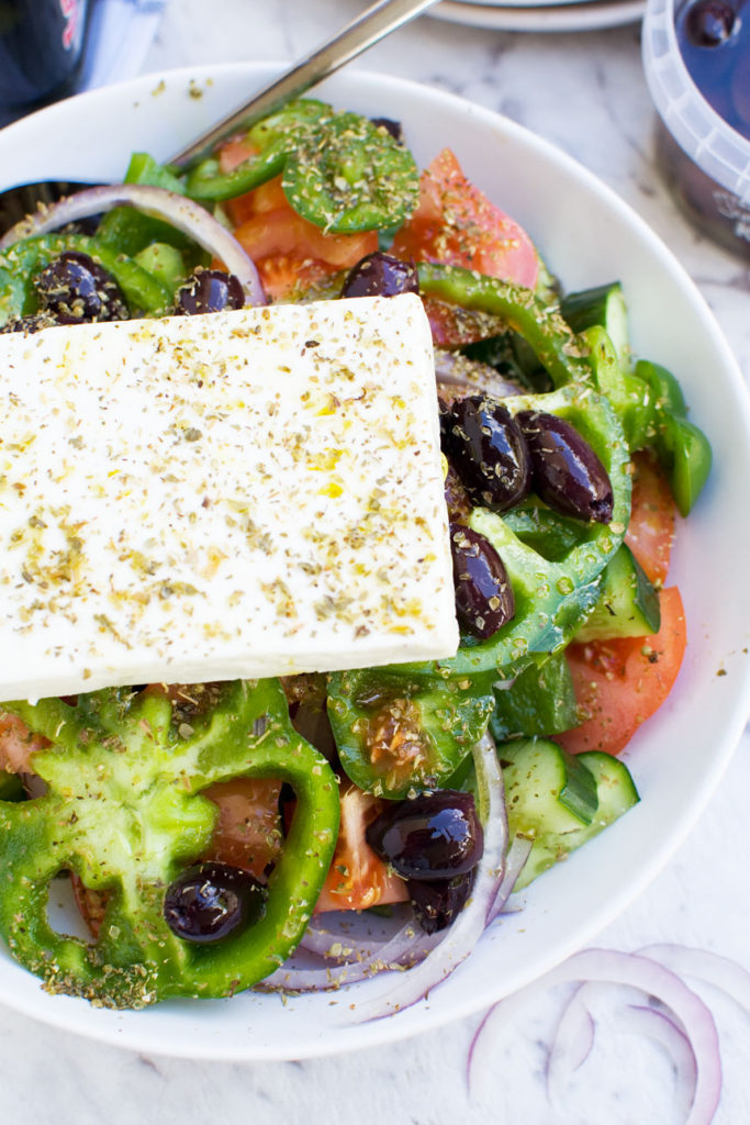 A closeup of a Greek salad in a white dish from above