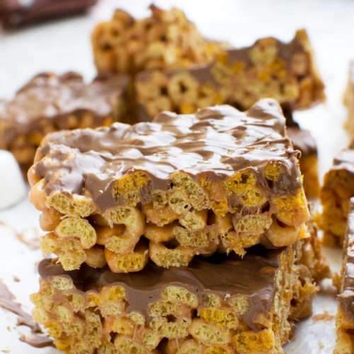 Two peanut butter cheerio bars stacked on top of each other, with others in the background