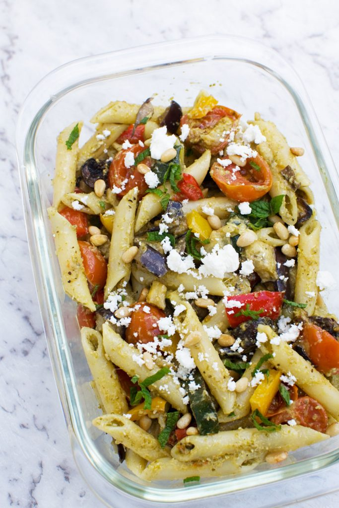 Mediterranean penne pasta salad in a clear glass container on a marble background