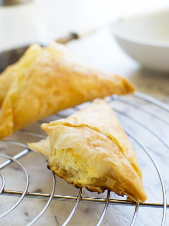 Tiropita or mini Greek cheese pies on a cooling rack