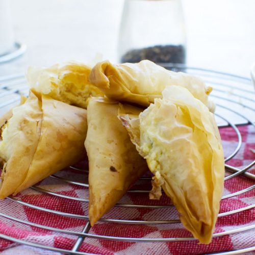 Tiropita or mini Greek cheese pies on a cooling rack and with a red and white checked tea towel in the background