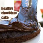 A spatula spreading avocado frosting onto a healthy chocolate cake