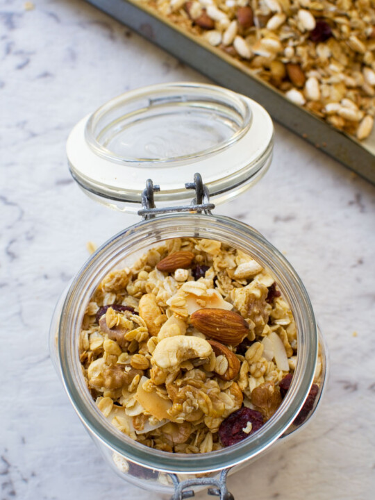 Basic homemade granola in an open glass container from above with a baking tray of granola in the background