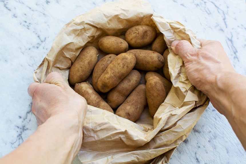 Small potatoes being held open in a brown paper bag