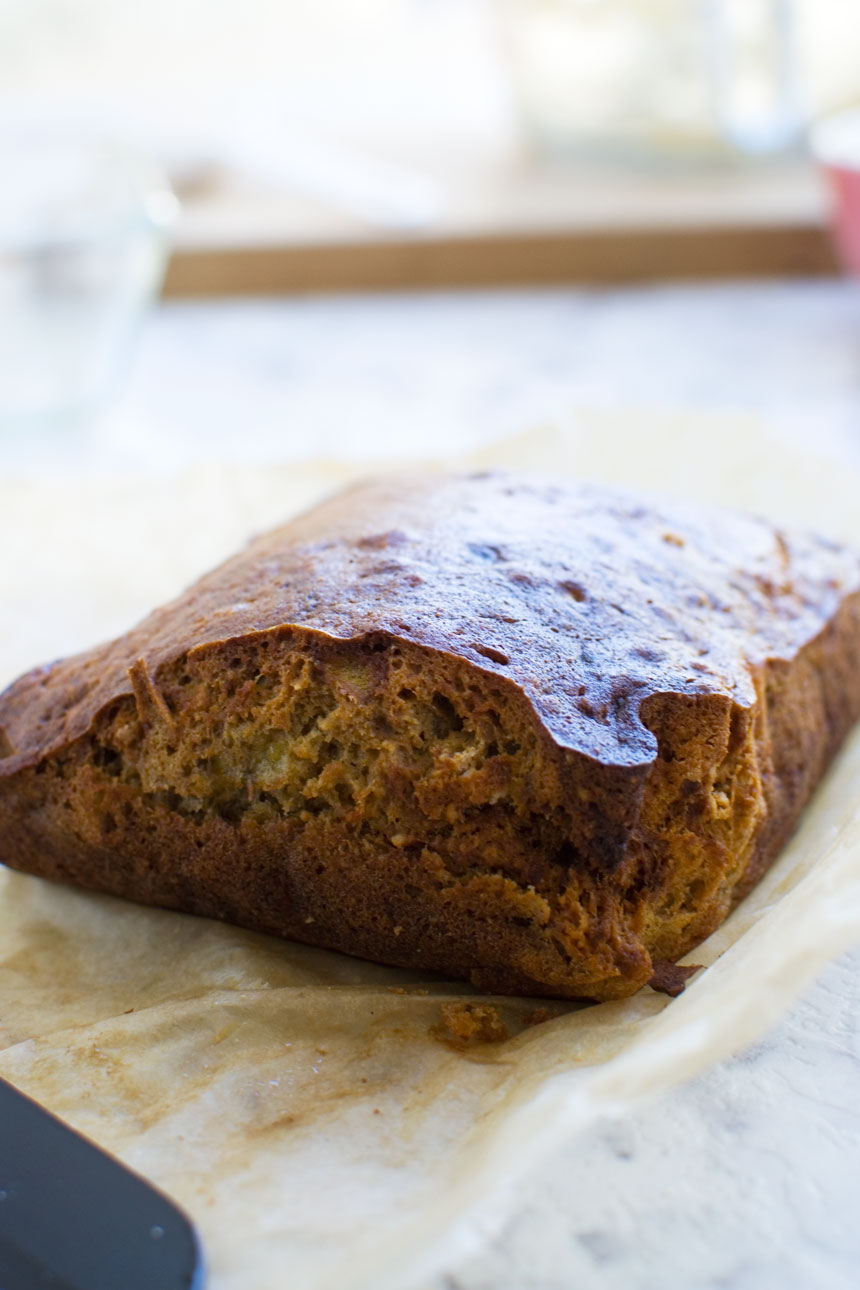 A close up of a mini banana bread just out of the oven on baking paper