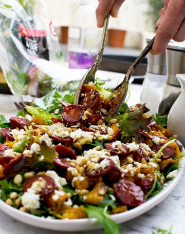 A person serving warm butternut squash, chorizo and feta salad with salad servers