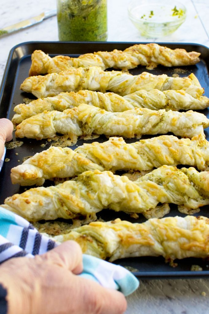 Supermarket copycat pesto and cheese twists side by side on a baking tray