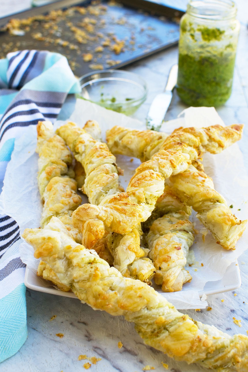 Supermarket copycat pesto and cheese twists on a white plate with a blue tea towel in the background