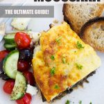 A piece of Greek moussaka with a Greek salad for Pinterest