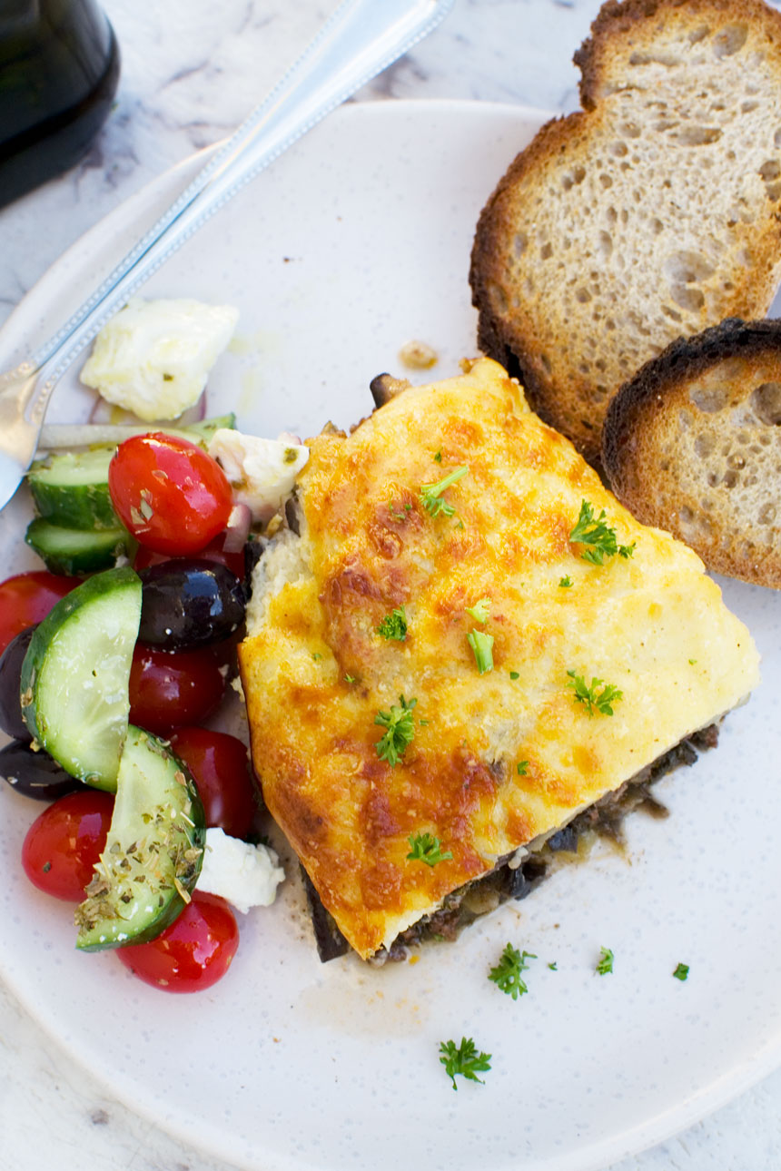 An overhead shot of a piece of easy moussaka on a white plate with bread and Greek salad