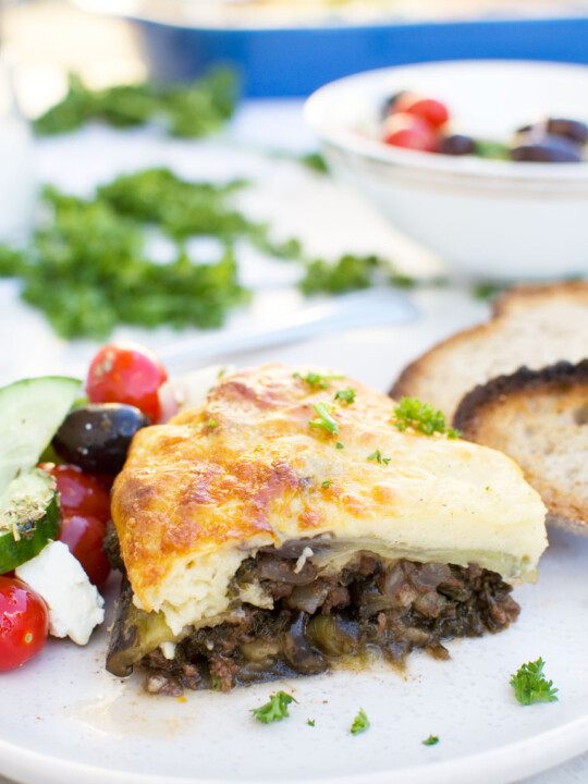 A piece of easy moussaka on a white plate with bread and Greek salad