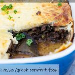 A Greek moussaka in a blue pan with a piece cut out