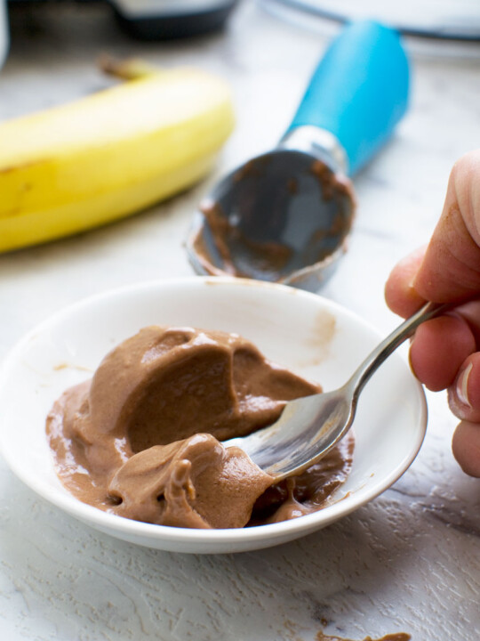 Someone eating 5-minute chocolate banana ice cream with a spoon with a banana and ice cream scoop in the background