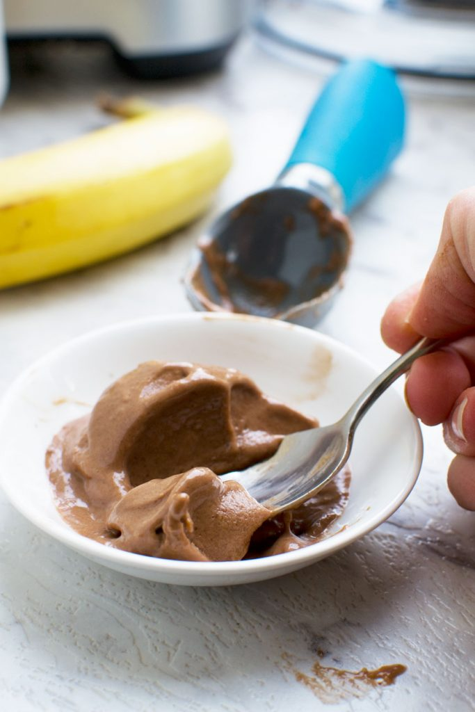 Somone eating 5-minute chocolate banana ice cream with a spoon - there\'s an ice cream scoop and a banana in the background