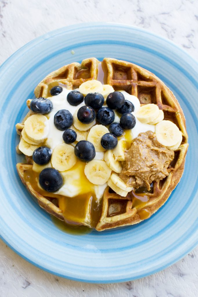 An overhead photo of a round waffle topped with yogurt, bananas, blueberries and peanut butter