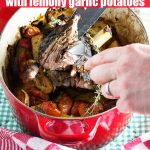 Greek style slow roasted Greek lamb and lemon potatoes being shredded in a red cast iron pot