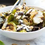 A white bowl filled with crispy brussels sprouts with tahini sauce and almonds