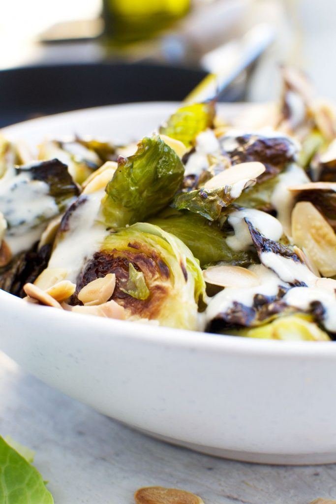 A close up of crispy brussels sprouts with tahini sauce and almonds in a white bowl