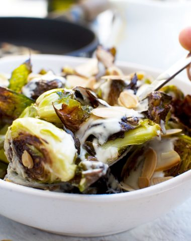 Someone serving themselves from a dish of crispy brussels sprouts with tahini sauce and almonds