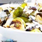 A close up of a white bowl of roasted brussels sprouts with tahini sauce and almonds for Pinterest