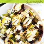 An overhead of a white bowl of roasted brussels sprouts with tahini sauce and almonds