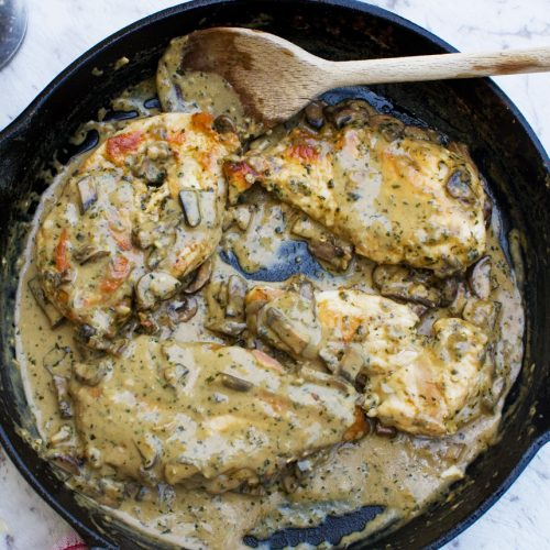 A frying pan of creamy pesto chicken from above with a wooden spoon in it