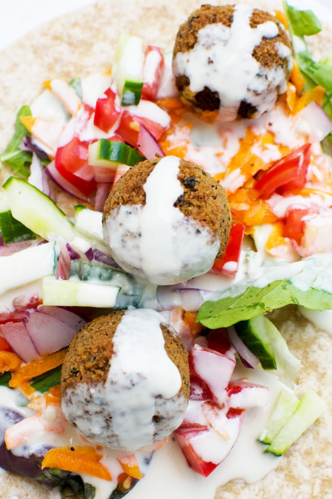 A close up of the inside of a falafel wrap drizzled with tahini dressing