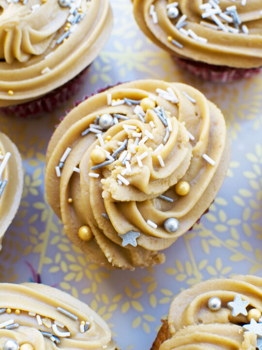 A top view of some gingerbread muffins with salted caramel icing on a decorative plate