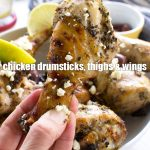 Someone holding up a Greek marinated chicken drumstick - image for Pinterest