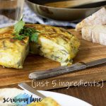 A Spanish omelette with a piece cut out of it on a wooden cutting board for Pinterest