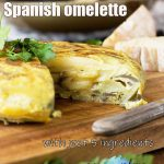 A Spanish omelette with a piece cut out of it on a wooden cutting board