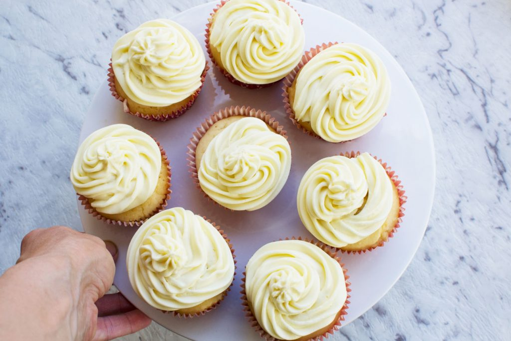 Someone holding a plate of healthier vanilla cupcakes with 2-ingredient frosting