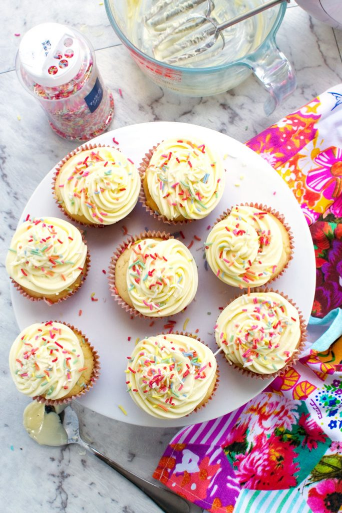 An overhead view of a plate of healthier vanilla cupcakes with a 2-ingredient frosting