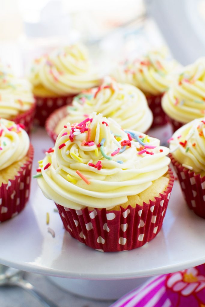 A vanilla cupcake with white chocolate cream cheese frosting and sprinkles on top and in a red spotted case