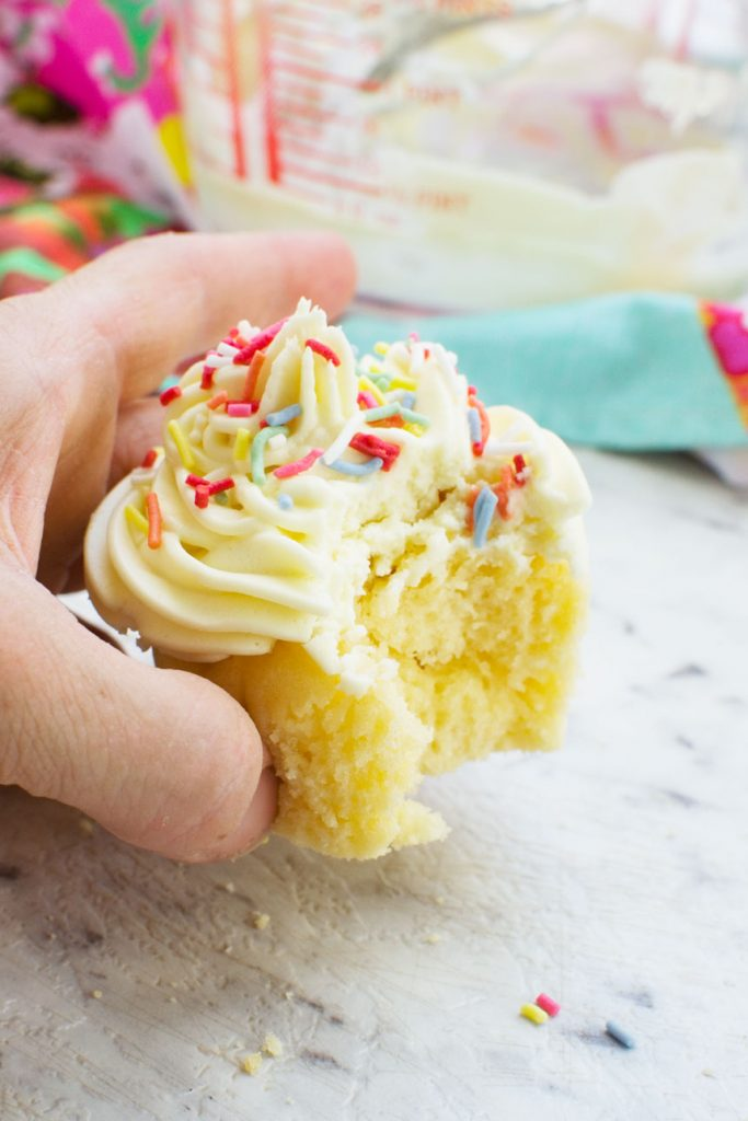 A close up of someone holding a vanilla cupcake with a bite out of it