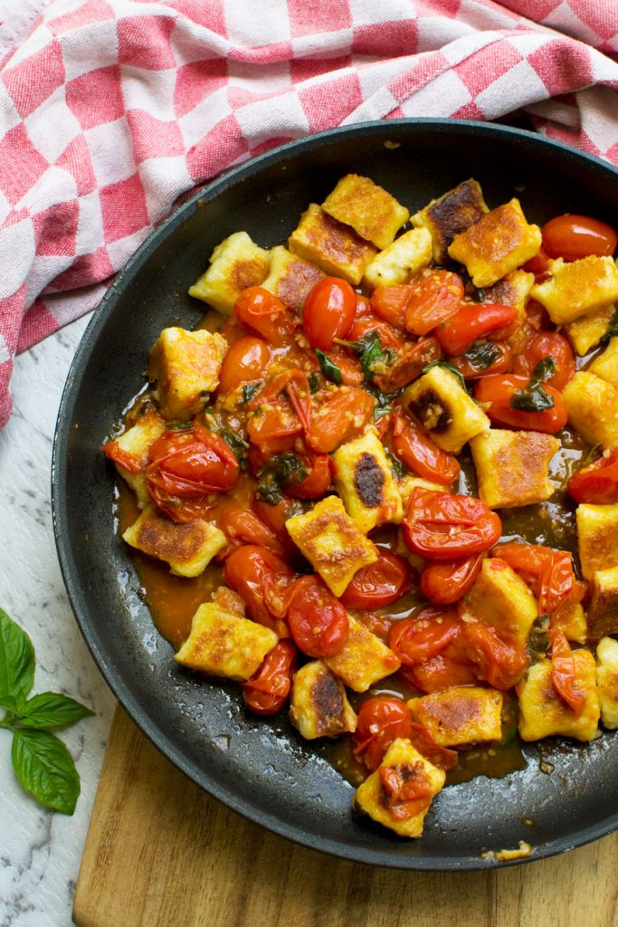 A pan of crispy gnocchi with cherry tomato sauce