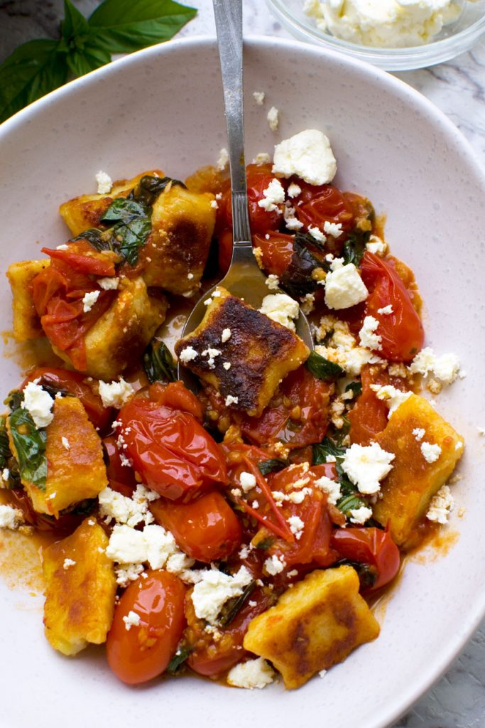 A close up of some crispy pan fried gnocchi in cherry tomato sauce in a white bowl with a spoon