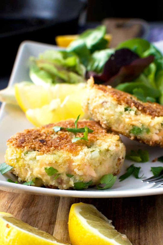 A plate of crispy salmon fish cakes with lemon and a simple salad