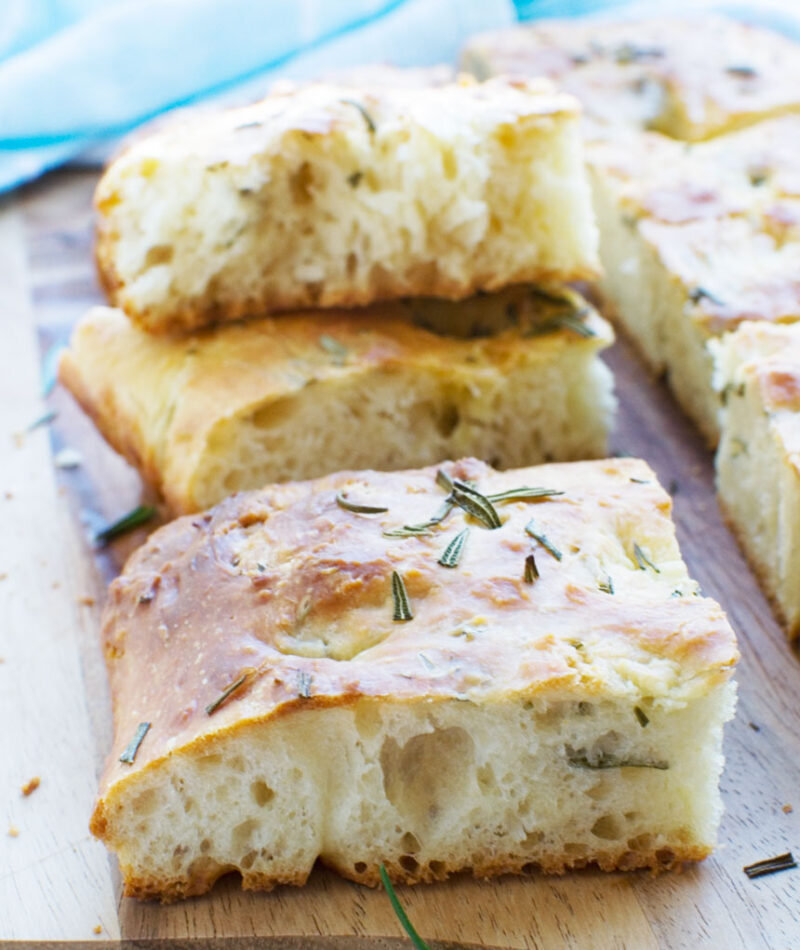 Squares of focaccia bread on a wooden cutting board