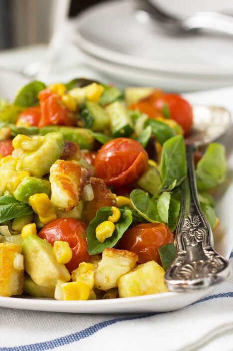 A crispy halloumi salad with avocado, corn and tomatoes on a white rectangular plate and a fancy serving spoon