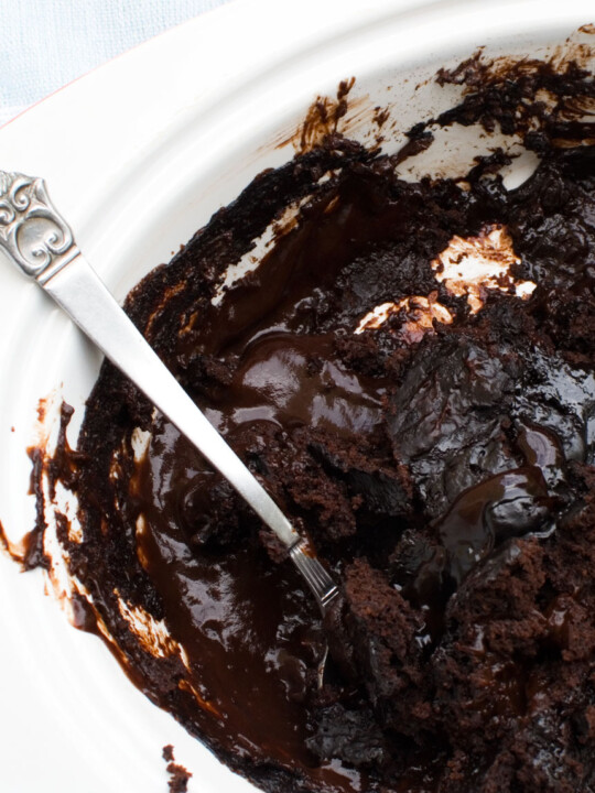 A close-up of a chocolate self saucing pudding with a decorative spoon in it