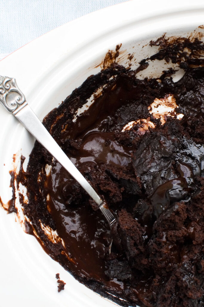 A close-up of a chocolate self saucing pudding with a spoon in it