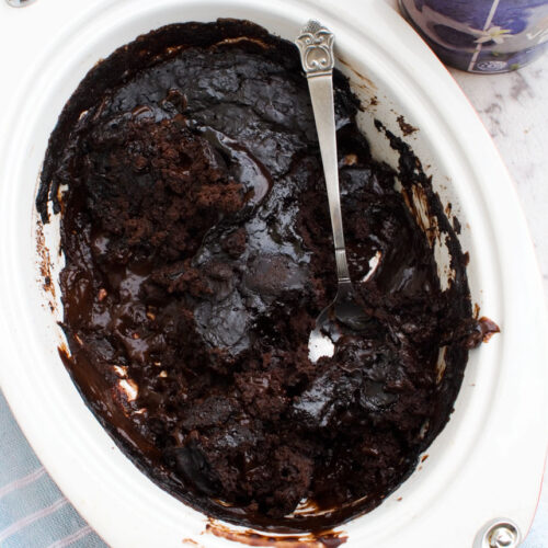 A dish of chocolate self saucing pudding with a spoon in it viewed from above
