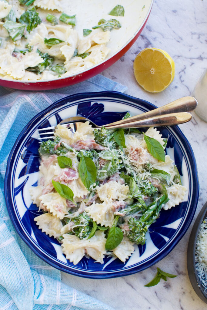 A plate of lemon ricotta pasta with broccoli and prosciutto from above