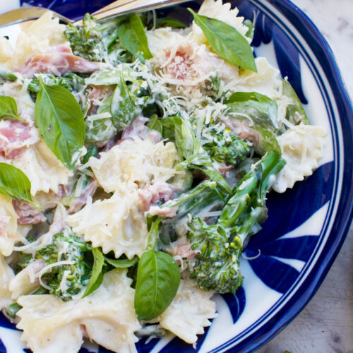 A close up of a blue bowl of lemon ricotta pasta with broccoli and prosciutto from above